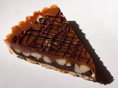 slice of chocolate caramel macadamia nut tart